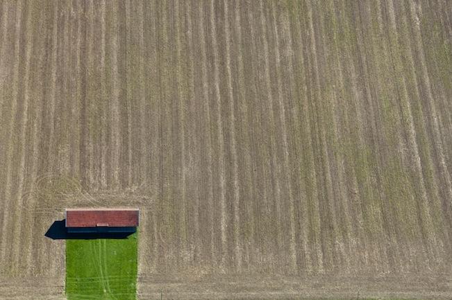 Luftaufnahme von einer Feldscheune mit grüner Zufahrt