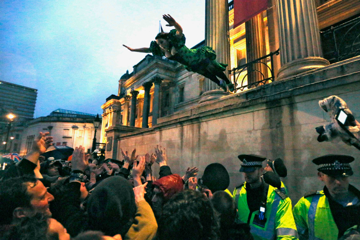 A reveller leaps into the crowd during an outdoor party celebrating the death of former British PM Thatcher in London