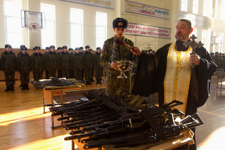Orthodox priest blesses rifles during a ceremony where new recruits receive their weapons at a military base of Belarussian Interior Ministry in Minsk