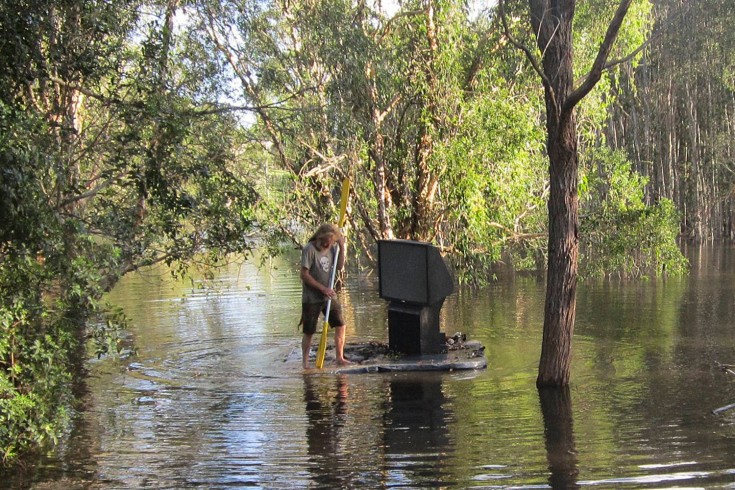 A man uses a spa cover to move a TV set through floodwaters at Cornubia