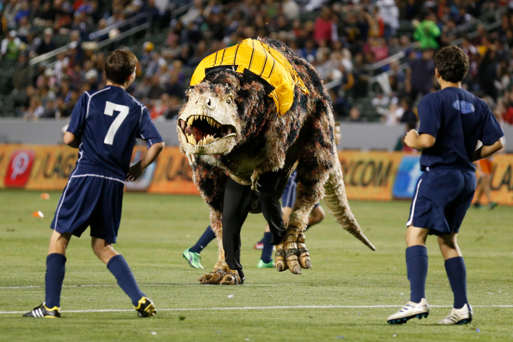 A Tyrannosaurus Rex dinosaur costume runs on the field as young boys play an exhibition soccer match during halftime of the MLS soccer game between the Los Angeles Galaxy and Seattle Sounders FC in Carson