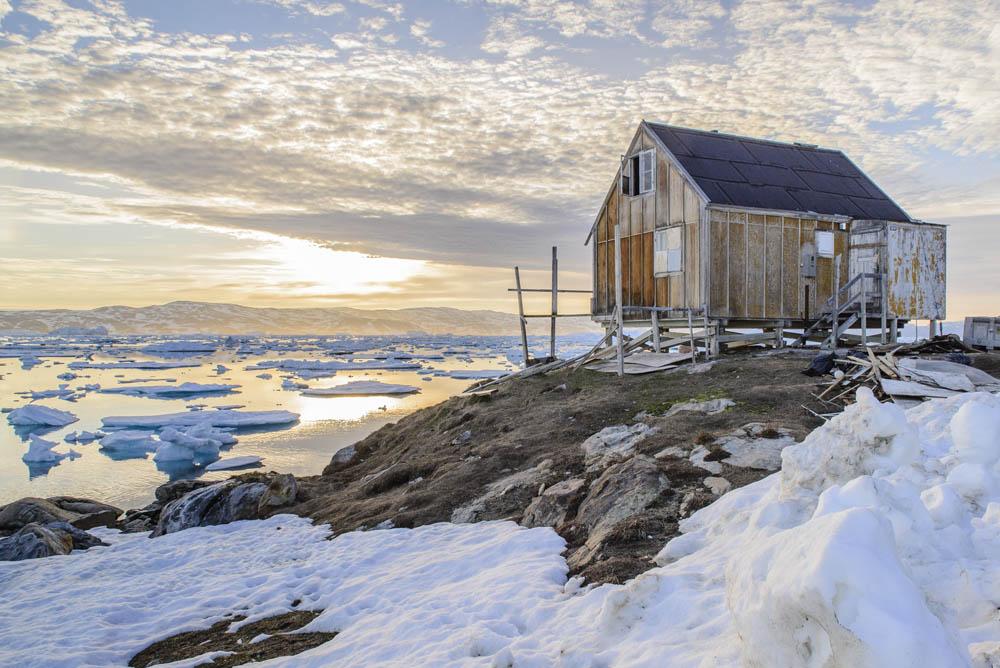 """Petite maison """"d'inuit moderne"""" au bord du fjord Sermilik au Groenland, au soir du 28 juin 2015. Reportage effectué dans le cadre d'un travail avec l'Union Internationale pour la Conservation de la Nature afin de montrer l'homme du Groenland dans la nature. Trois expéditions au Groenland ont déjà été réalisées depuis 2014, afin d'effectuer ce reportage. Ces expériences me permettent de colliger les témoignages nécessaires à une compréhension éclairée des enjeux liés à la protection de l'environnement, et à la sauvegarde des us et coutumes arctiques."""